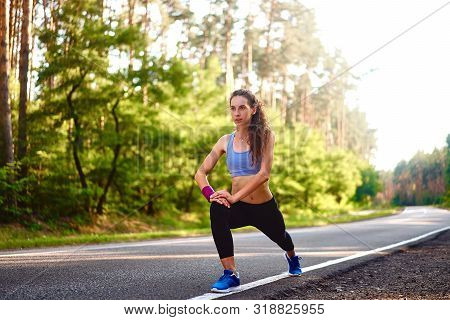 Young Woman Warming Up At Forest Road Before Jogging. Attractive Girl Stretching For Running Exercis