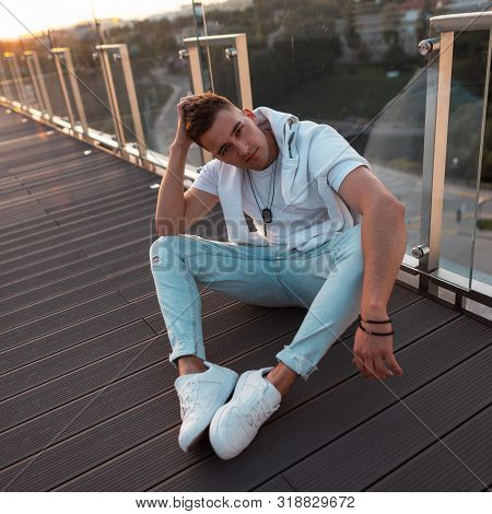 Modern Nice Young Man Model In Fashionable Summer Clothes Sits On A Wooden Floor On A Summer Outdoor