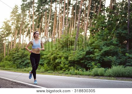 Beautiful Caucasian Young Girl Athlete Runs Sunny Summer Day On Asphalt Road In The Pine Forest. Wom