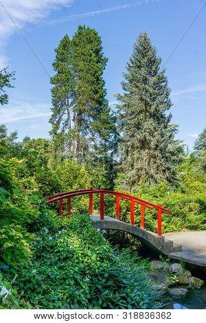 A View Of A Red Walking Bridge In A Graden In Renton, Washington.