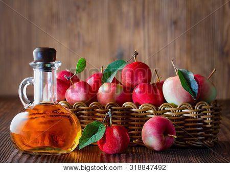 Apple Cider Vinegar In A Glass Bottle. Apples In A Wicker Basket. The Photo.
