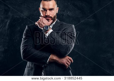 Sceptical Bearded Man In Suit And White Shirt Is Posing For Photographer At Dark Studio.