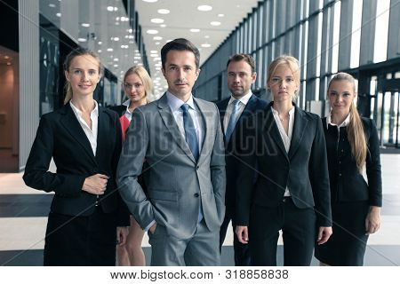 Portrait Of Group Of Young Excited Business People In Formal Wear Standing In Office