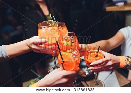 Women Raising A Glasses Of Aperol Spritz At The Dinner Table.