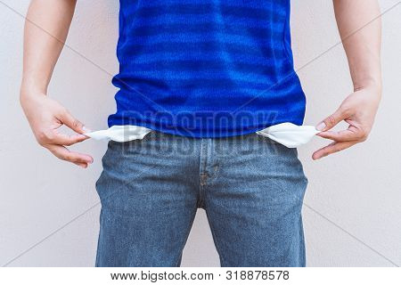 Man Showing His Empty Pockets On Wall Background.