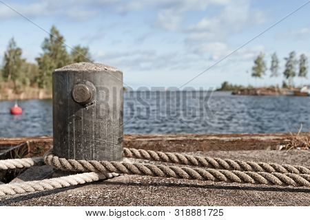 An Old Metal Bollard On A Pier At The Fishing Harbour Of The Town Of Kalajoki, Finland. The Ropes Be