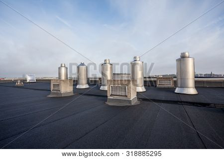 Four Chimney On The Flat Roof Off A Big Building In The City