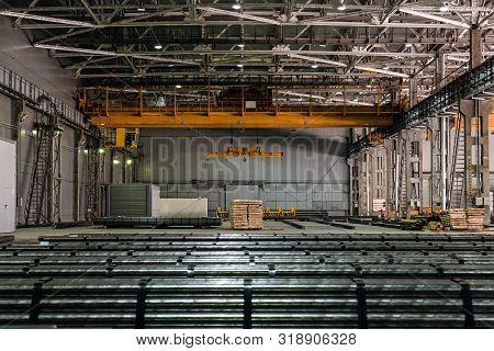 Yellow Overhead Crane In Engineering Plant Shop. Industrial Metalwork Production Hall And Warehousin