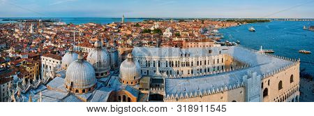 Aerial panorama of Venice with St Mark's Basilica and square and Doge's Palace on sunset from St Mark's Campanile bell tower, Venice, Italy. Camera horizontal pan