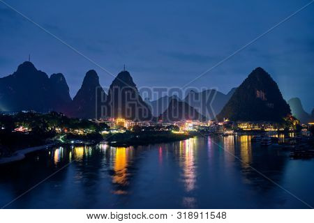 View of Yangshuo town illuminated in the evening with dramatic karst mountain landscape in background over Li river. Yangshuo, China
