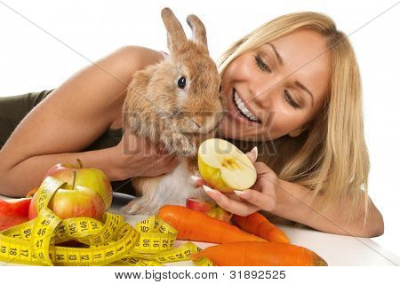 A girl giving fresh vegetables to young rabbit bunny,  isolated on white