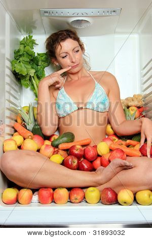 Woman sitting in a fridge in the lotus position surrounded by fruits