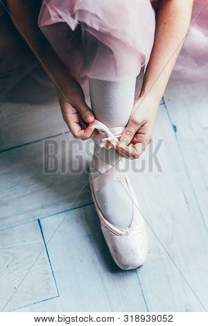 Hands Of Ballerina In Pink Tutu Skirt Puts On Pointe Shoes On Leg In White Light Hall. Young Classic