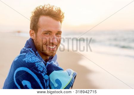 Smiling handsome young man beauty portrait on beach at sunset looking at camera laughing, healthy grin face of happy model in towel.
