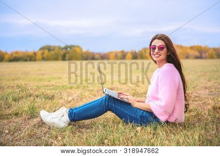A beautiful young woman is sitting on the grass in the coutryside with a laptop. Lifestyle, autumn fashion. Nature and gadgets.