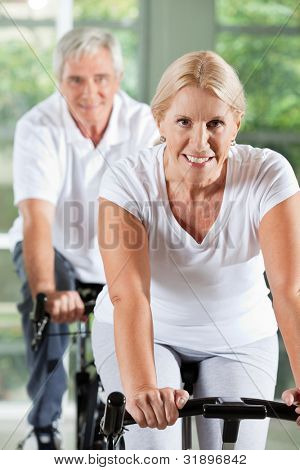 Happy senior people exercising on bikes in gym