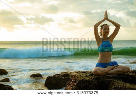 Young woman sitting on the rock, meditating, practicing yoga and pranayama, raising arms with namaste mudra at the beach. Lotus yoga pose with namaste mudra. Copy space. Yoga retreat in Bali.