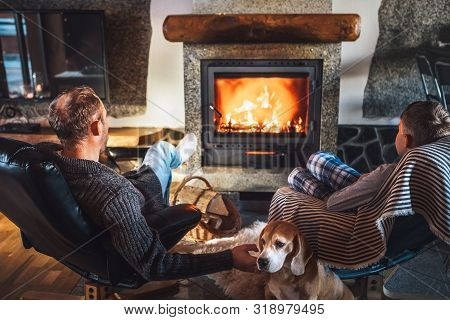 Father With Son Sitting In Comfortable Armchairs In Their Cozy Country House Near Fireplace And Enjo