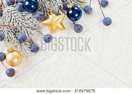 Christmas Background With Blue Berries, Green Xmas Tree Twig And Gold Decoration On White Snow