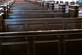 Cathedral benches. Rows of pews in christian church. Heavy solid uncomfortable wooden seats. poster