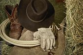 Western Cowboy hat with cowboy boots, leather gloves, leather chaps and a roper's rope on hay in a barn poster