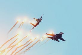 Two Combat Fighters Jet Perform An Air Battle With The Firing Of Warheads With Explosions