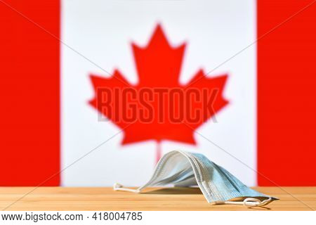 A Medical Mask Lies On The Table Against The Background Of The Flag Of Canada. The Concept Of A Mand