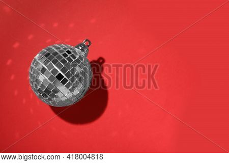 Bright Shiny Disco Ball On Red Background, Top View. Space For Text