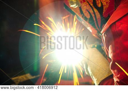 Close-up Welder Technician Wear Protection Bodysuit  And Safety Mask Working With Workpieces Via Wel
