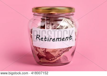 Money Box With Word Retirement On Sticky Note Paper. Dollars In Glass Money Jar With Savings Label,