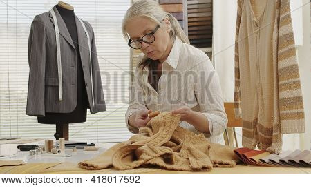 Woman Dressmaker Working In Workshop With Tailoring Mannequin, Choose The Spool Thread For The Sweat