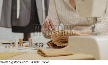 Woman Dressmaker Working In Workshop With Tailoring Mannequin, Sews By Hand The Sweater. Closeup, Wi