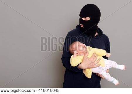 Man Thief In Balaclava Kidnapped Newborn Crying Baby, Runs Away, Looks Back While Holding Child In H