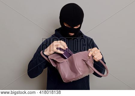 Young Male Burglar Steals Woman's Handbag, Opens Bag And Looking Inside, Pulls Out Wallet, Wearing B