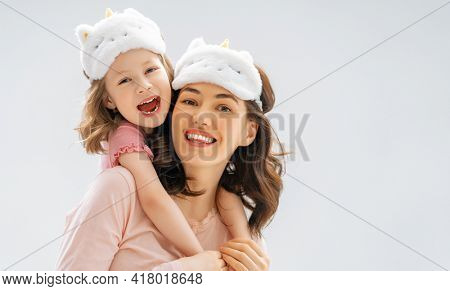 Happy mother's day! Daughter and mother are hugging standing on light grey background. Family togetherness.