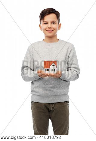mortgage, real estate and accommodation concept - smiling boy holding house model over white background