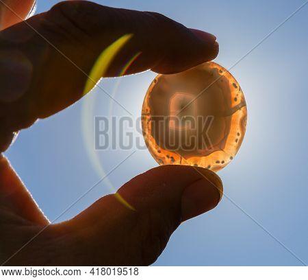 Semi-precious Stone Agate In Hands In Backlight
