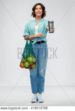 sustainability, food shopping and eco friendly concept - happy smiling woman in turquoise shirt holding reusable net bag with fruits and vegetables and tumbler or thermo cup over grey background