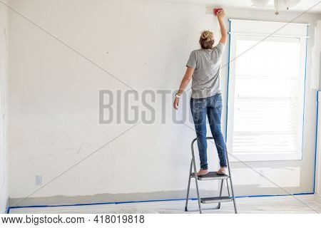 Rear view of a Woman re-painting the interior of her home. Lots of copy space on a gray and white bedroom wall
