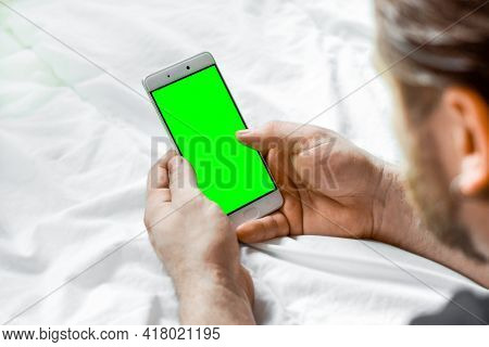 Young Bearded Man Using Green Chroma Key Screen Phone, Relaxing In A Bed. Guy Uses Green Mock-up Scr