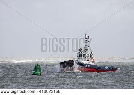 Rotterdam, Netherlands - 2021-04-07: Tugboat Sd Rebel Sailing Past A Buoy Near The Port Of Rotterdam