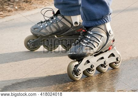 Close-up Of Roller Skates On Childrens Feet. The Rollers Are Old, Scratched, Worn Out, Running On An