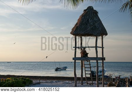 A Man Sitting In A Rustic Wooden Hut On A Beach On The Island Of Holbox In Mexico Observes The Horiz