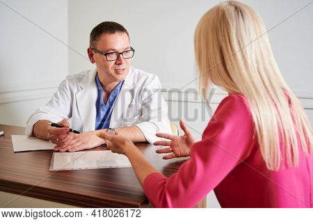 Male Surgeon In White Lab Coat Sitting At The Table With Papers And Talking With Female Patient In O