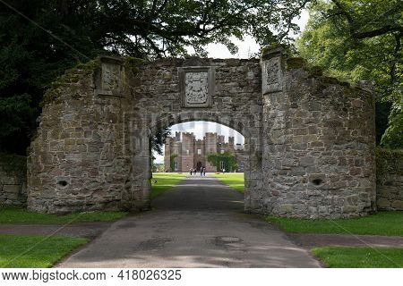 Perth, Scotland - August 12, 2019: Archway Of Scone With Scone Palace In The Background With Tourist