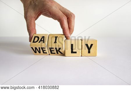 Daily Or Weekly Symbol. Businessman Turns Wooden Cubes And Changes The Word 'weekly' To 'daily'. Bea