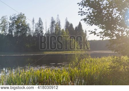A River Or Lake With A Calm Smooth Surface On A Quiet Summer Day In The Evening.