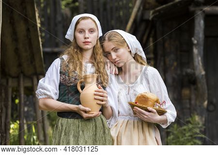 Rural Style Concepts. Pair Of Young Beautful Caucasian Girlfriends In Traditional Rural Outfit  Posi