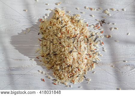 Rice Grains On A Wooden Surface. A Mixture Of Different Varieties Of Rice. Background. Copy Space.