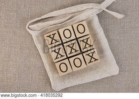 Tic Tac Toe Wood Blocks With Bag. Play On A Gray Linen Background, Also Known As Tic-tac-toe.